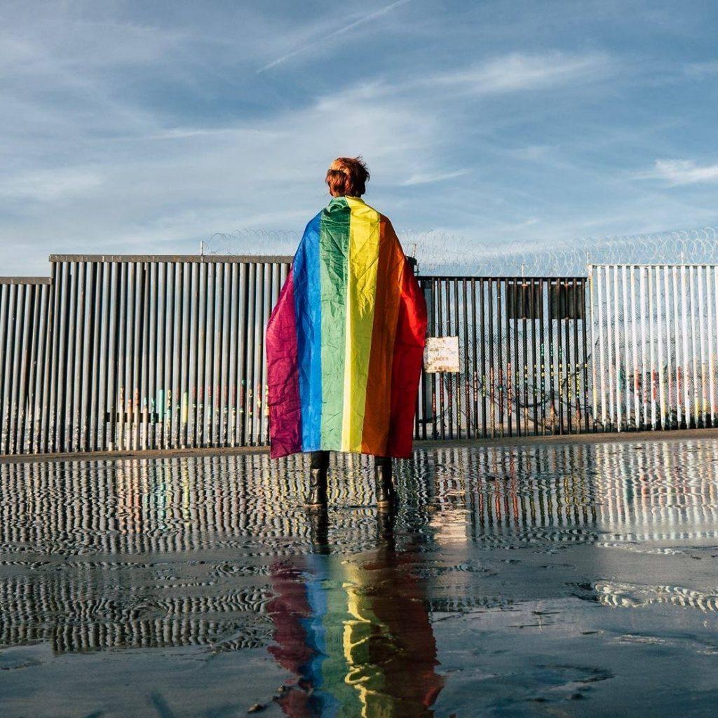 Persona con bandera LGBT+ en la frontera Tijuana- San Diego.